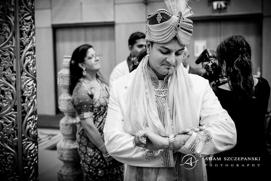 Asian Wedding Photographer karan looks at his watch during wedding