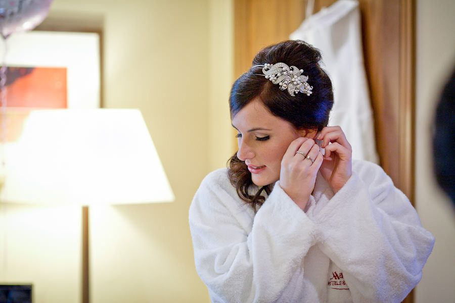 The bride in the bathrobe wears earrings