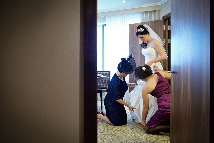 bridemaids help the bride to wear the wedding dress