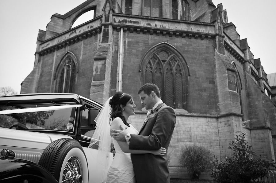 romantic photo portrait of the married couple in front of the gothic church in teddington