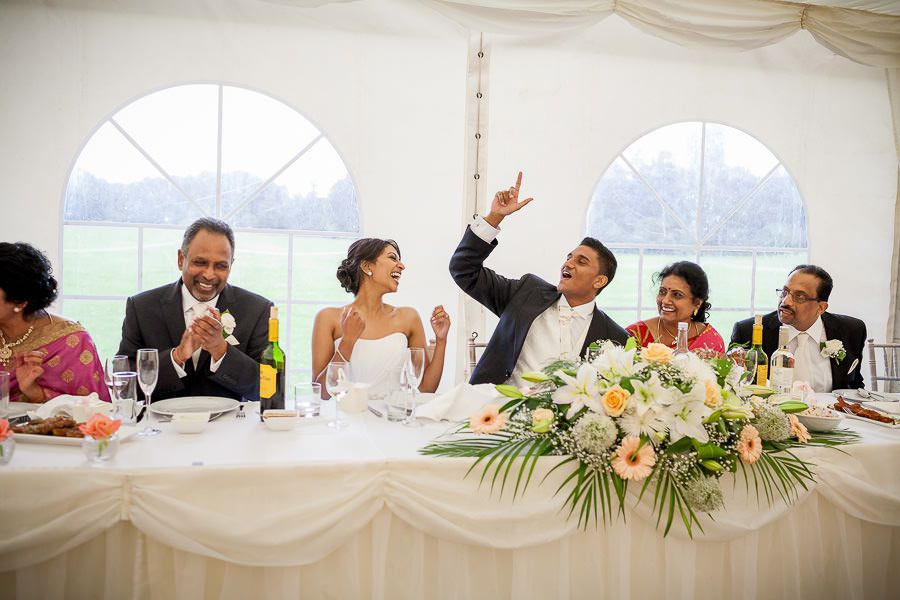 happy married couple and their weddding guest at the table