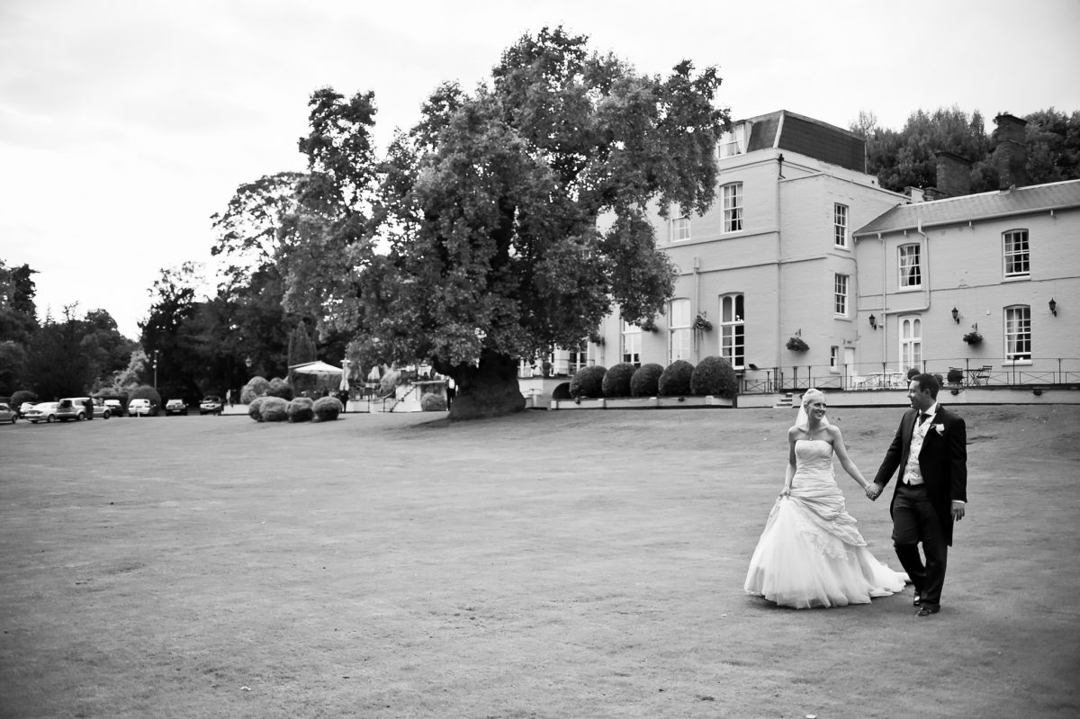 Taplow House Hotel Wedding Photographer the couple walking in front of the venue