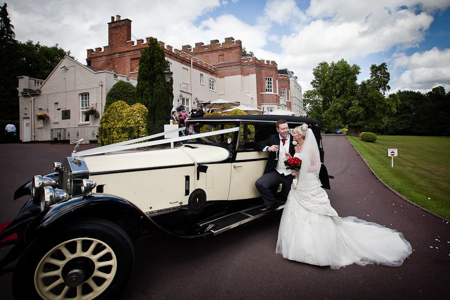 married couple Emma and Matt in front of the car on the background the taplow house hotel in berkshire