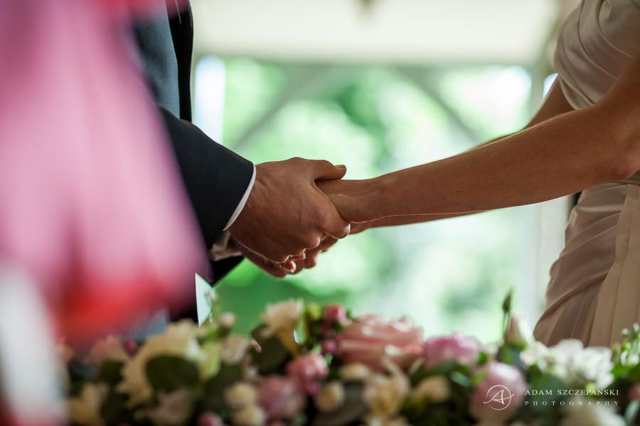 married couple hold their hands during the wedding