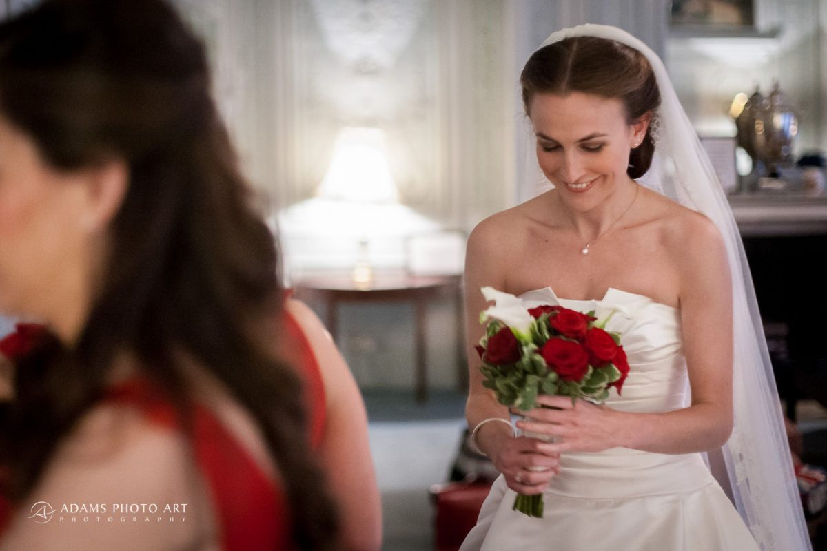 happy bride holds the red roses