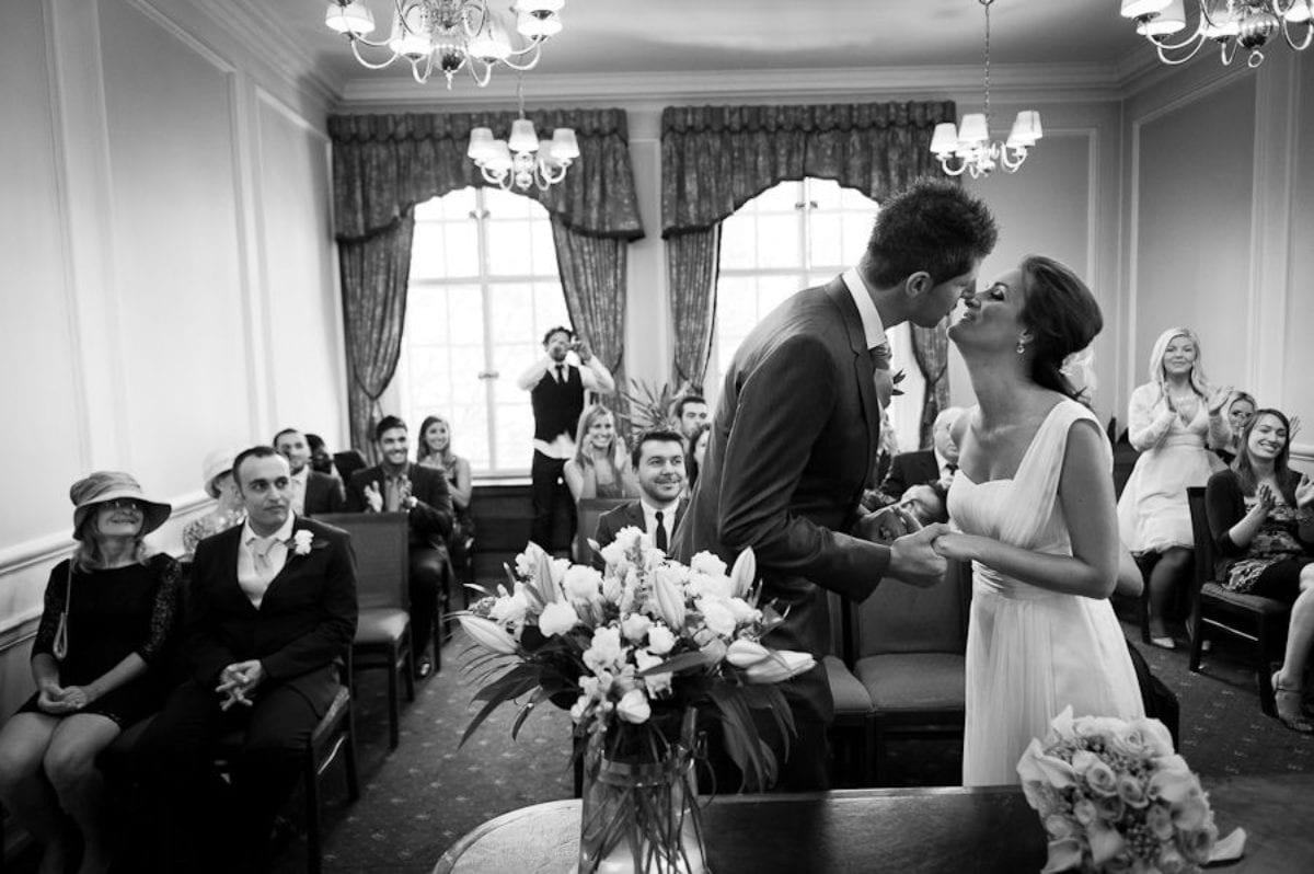 black and white photo of the married couple first kiss during the wedding ceremony
