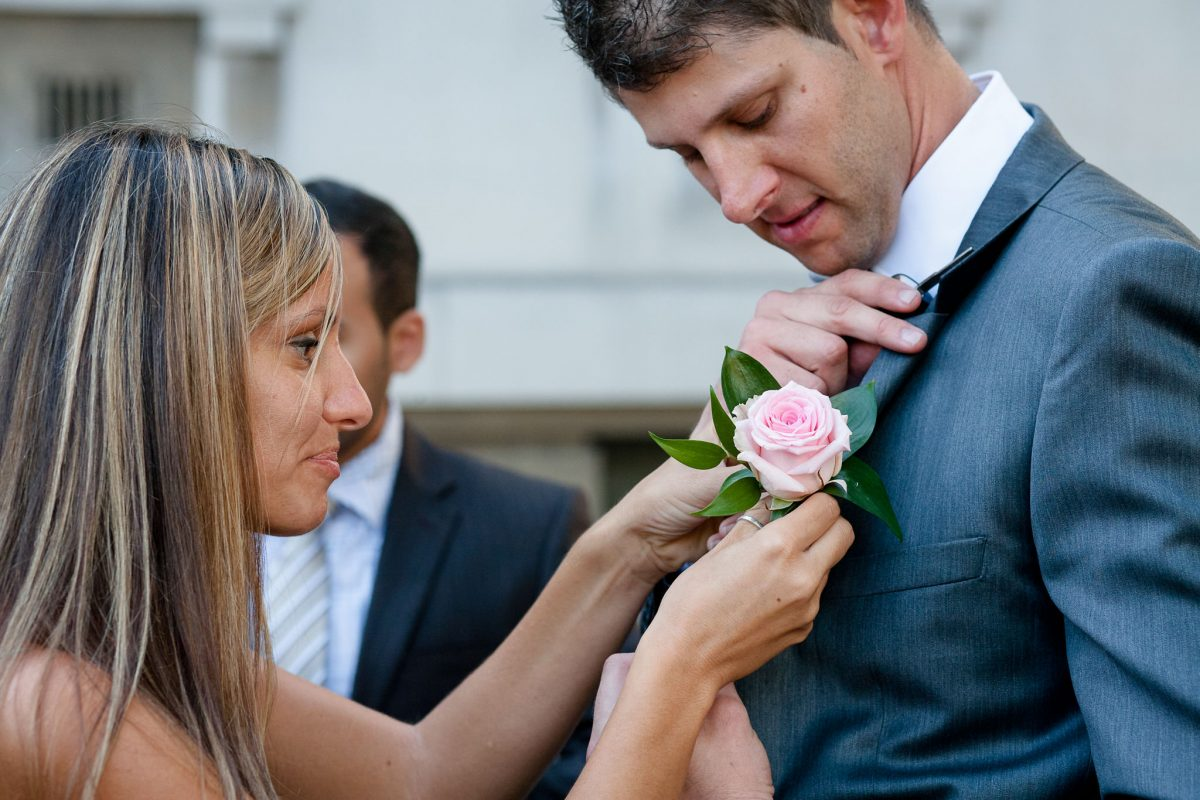 Old Marylebone Town Hall wedding groom is having his button flower pined in