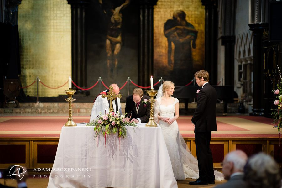 married couple and the priest signs the wedding act