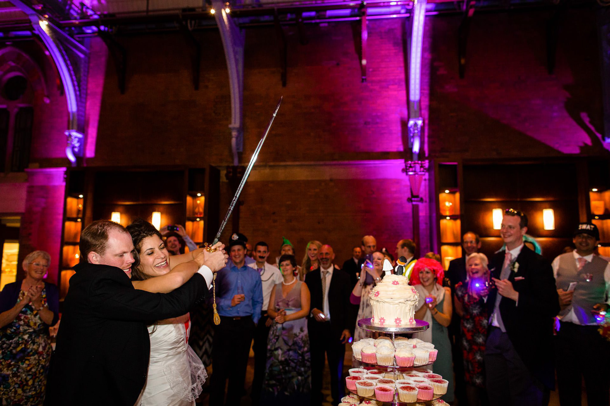 St. Pancras hotel wedding cutting the cake with a sword