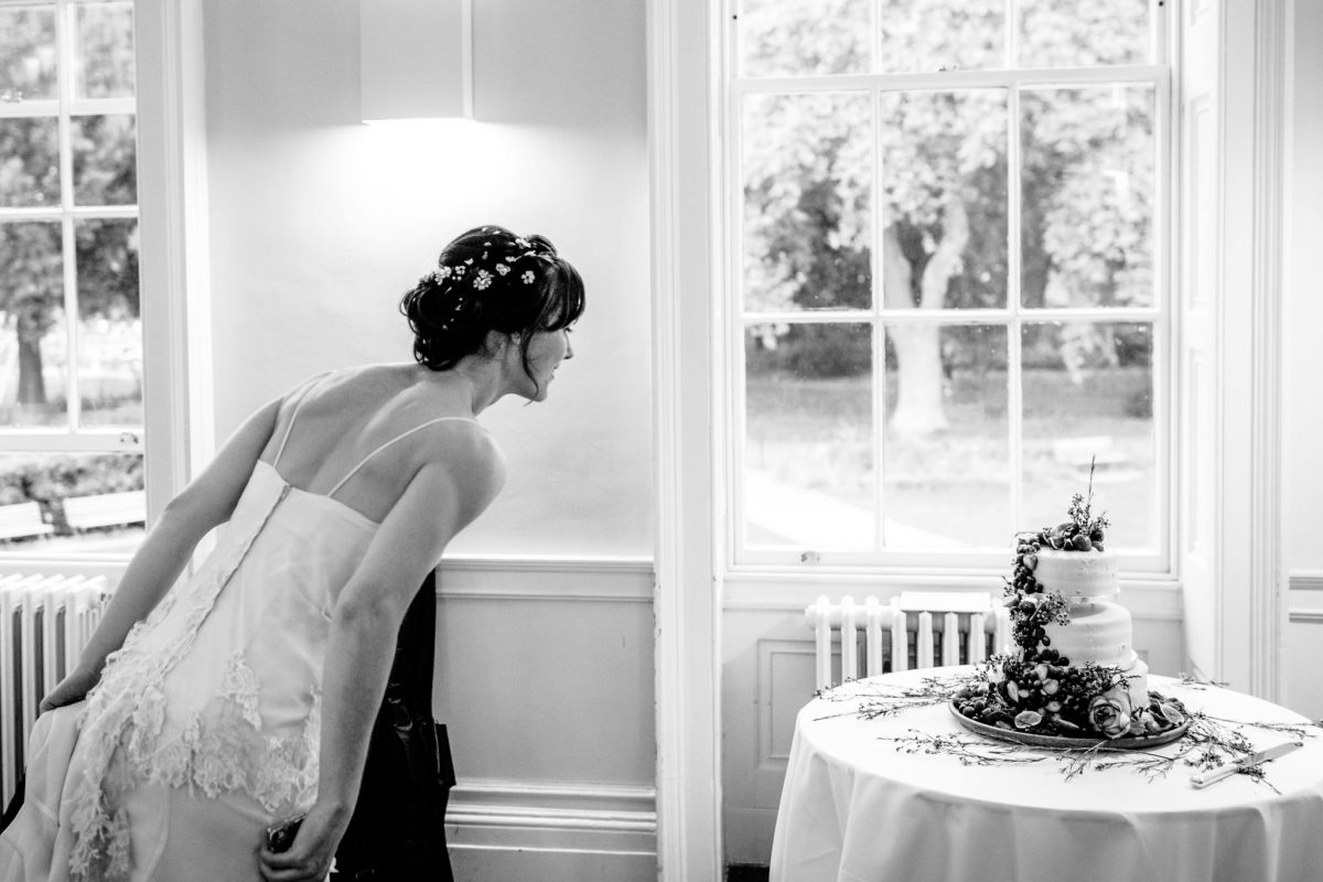Clissold House wedding bride checking on the cake