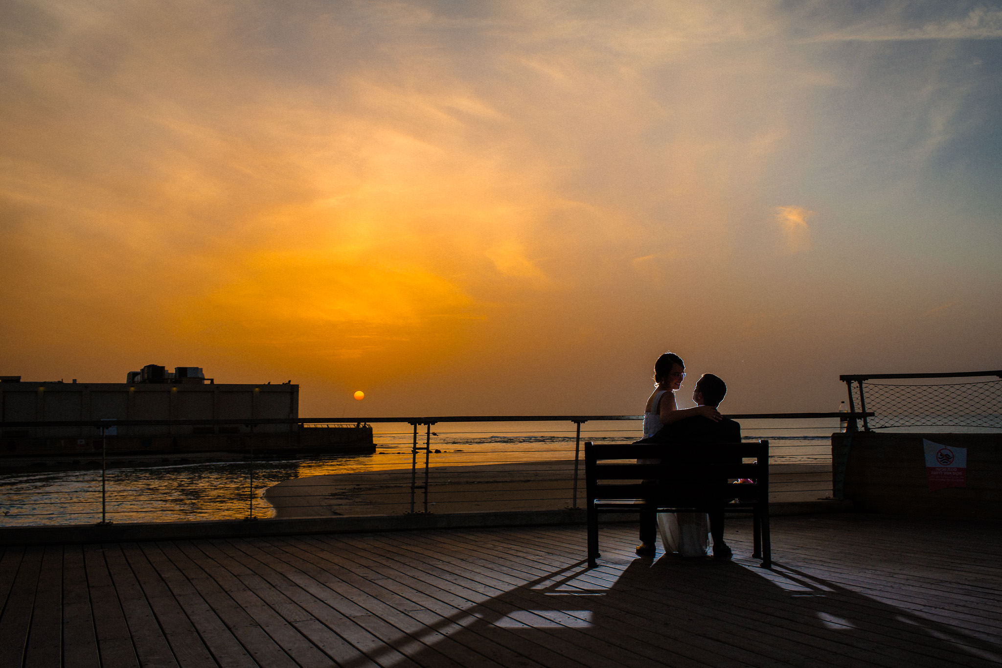 Jewish Wedding Photographer Israel couple seating on a bench by the sunset in Tel Aviv