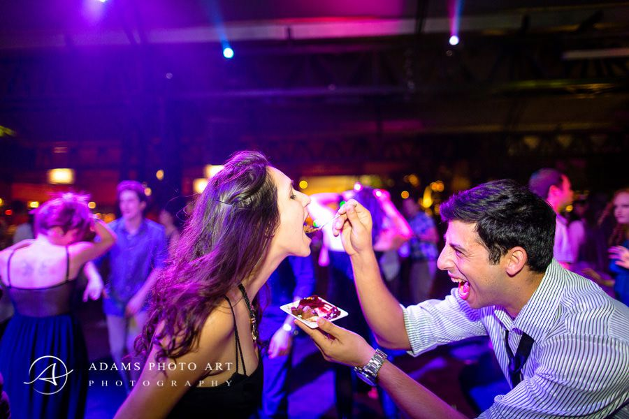 Man feeding a woman on the background of fun on the dance floor