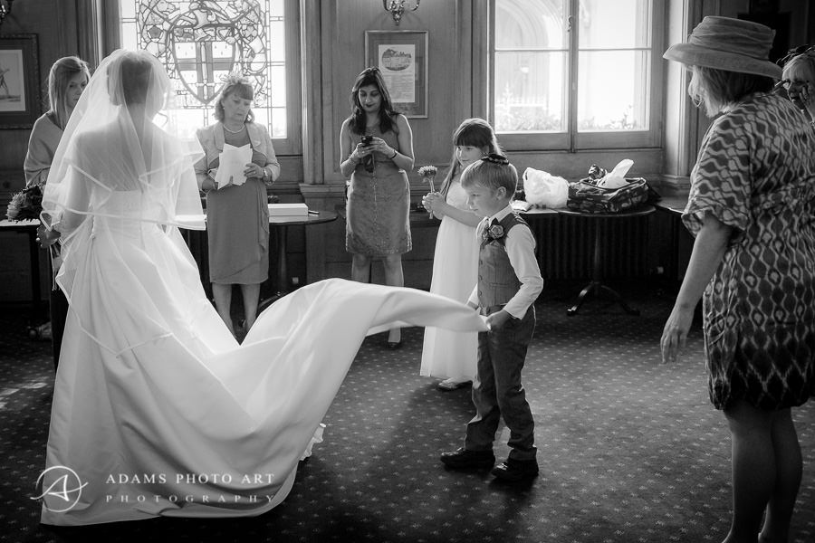 boy keeps the train of the wedding dress