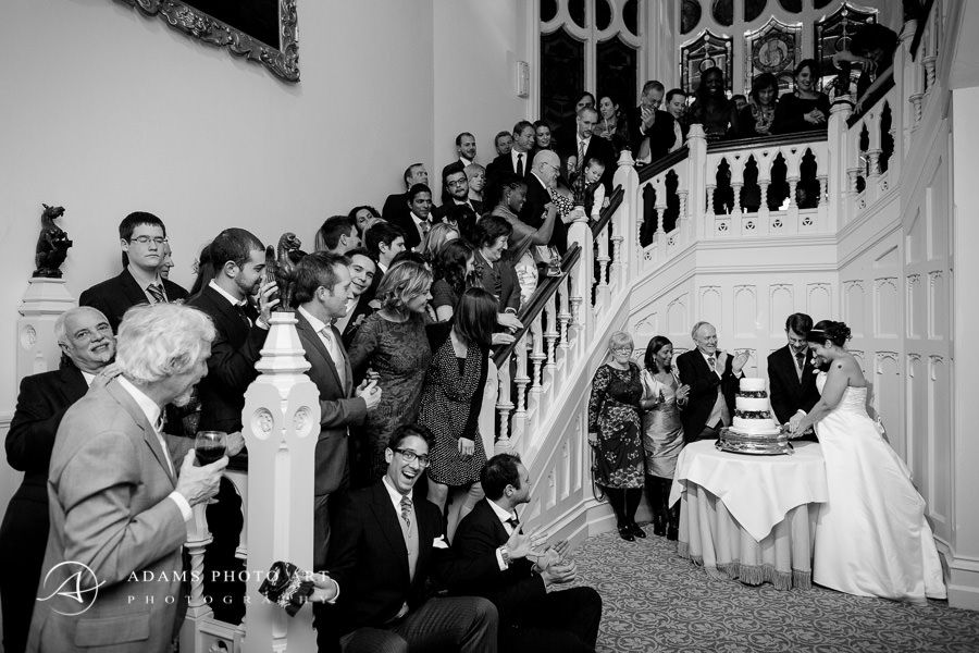 group picture of the married couple cutting their wedding cake and the guests watching at the stairs