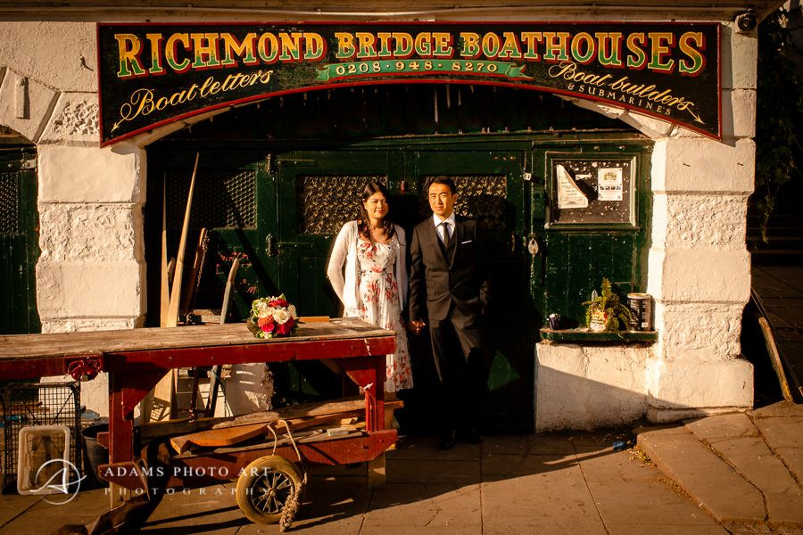 couple in front of the richmond bridge boathouses