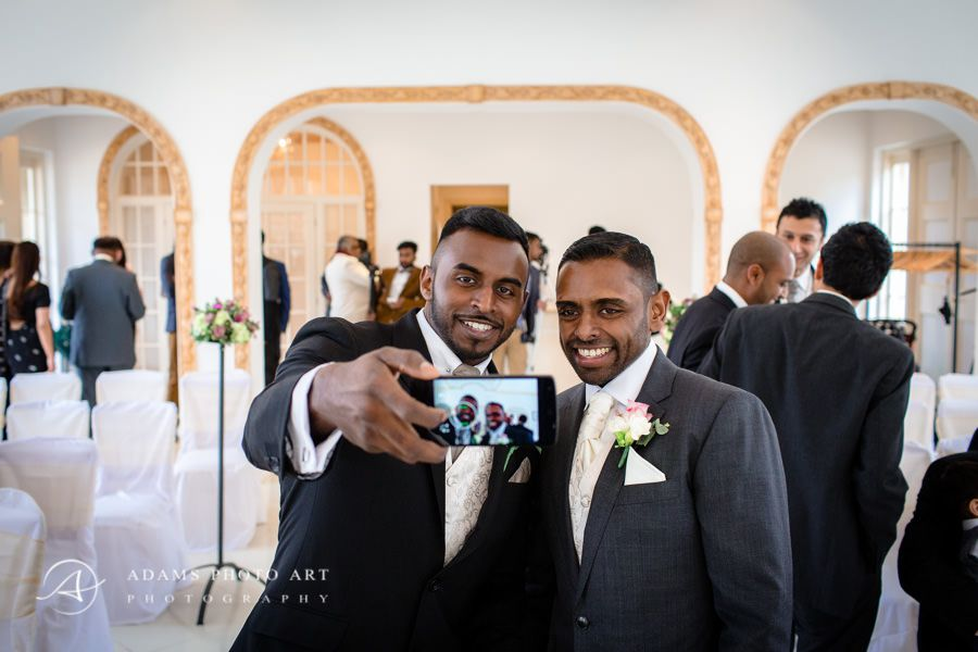 groom taking photo with his groomsman
