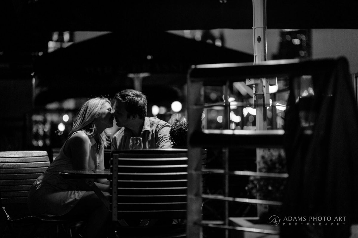 the engaged couple are having a kiss in the restaurant by the river Thames
