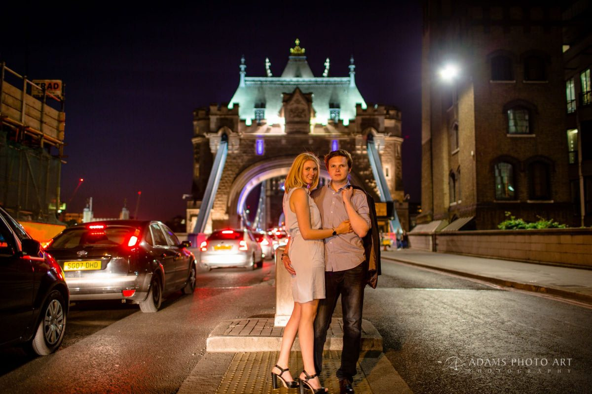 the engaged couple is standing in front of the Tower Bridge
