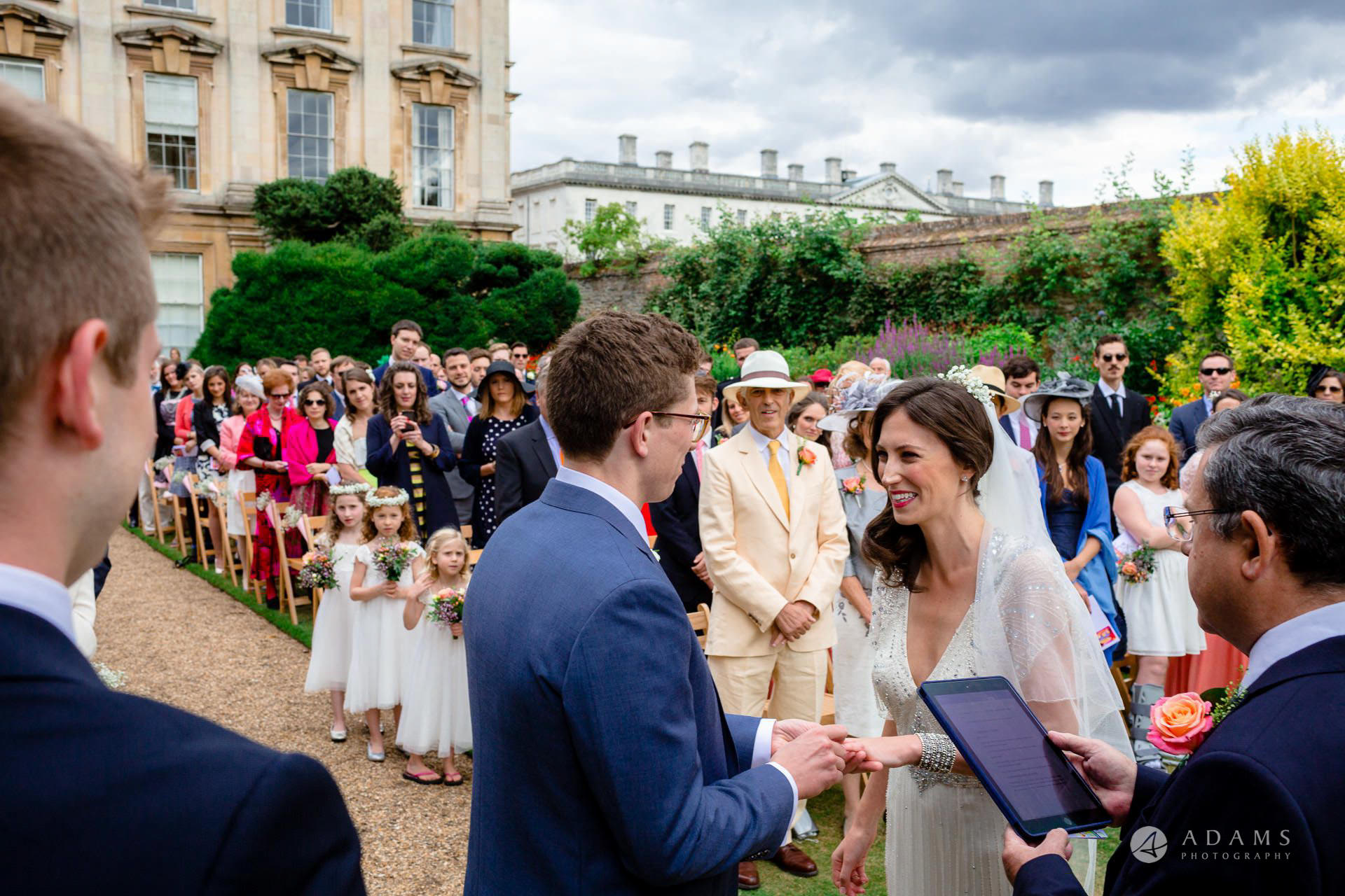 Clare College wedding groom puts a ring on the bride finger