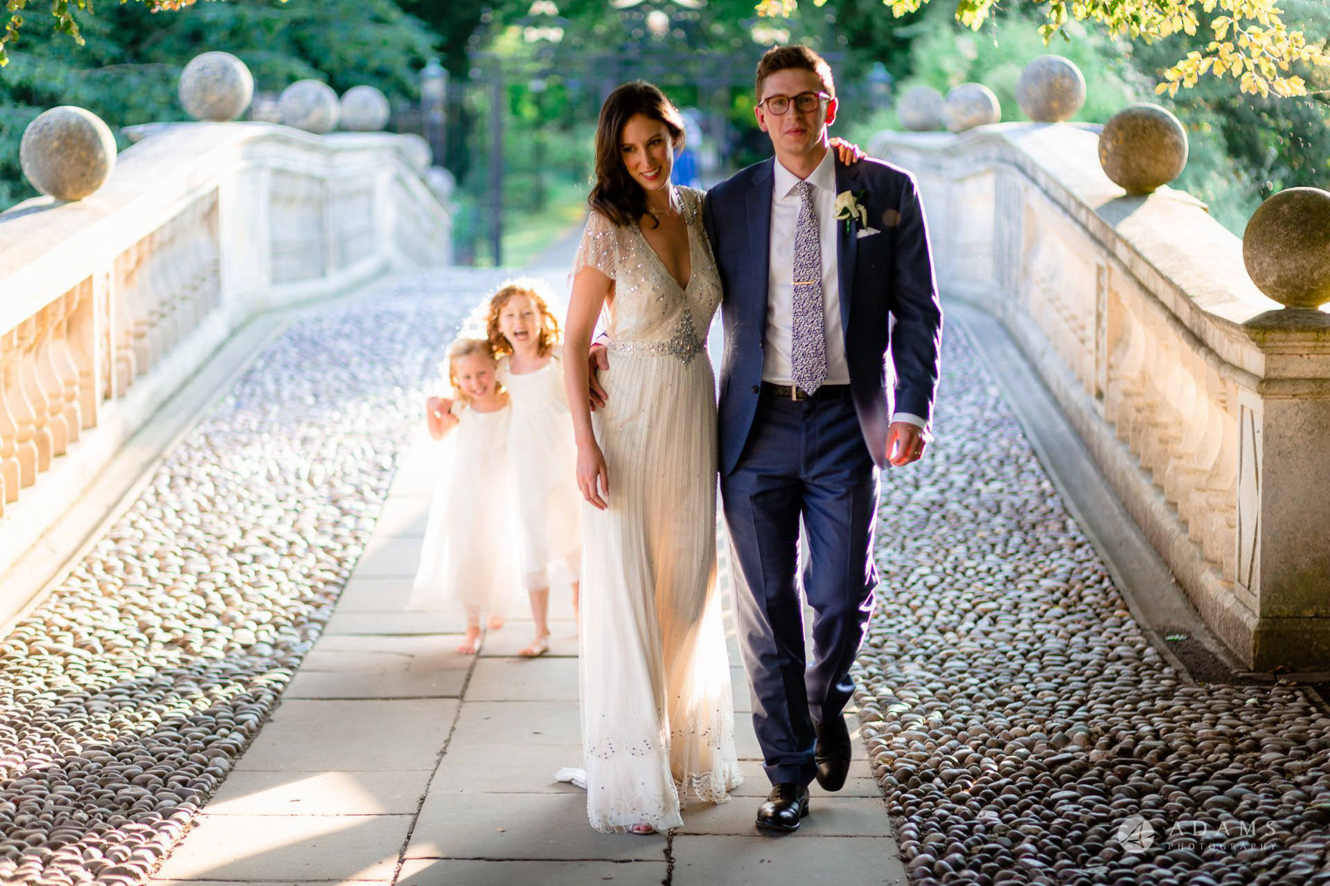 Clare College wedding married couple walk on the bride with flower girls