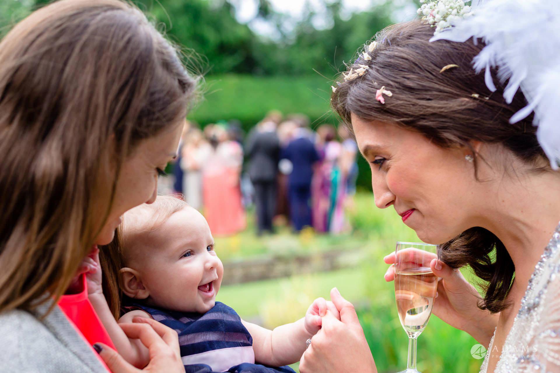 Clare College wedding photos bride smiles to a baby