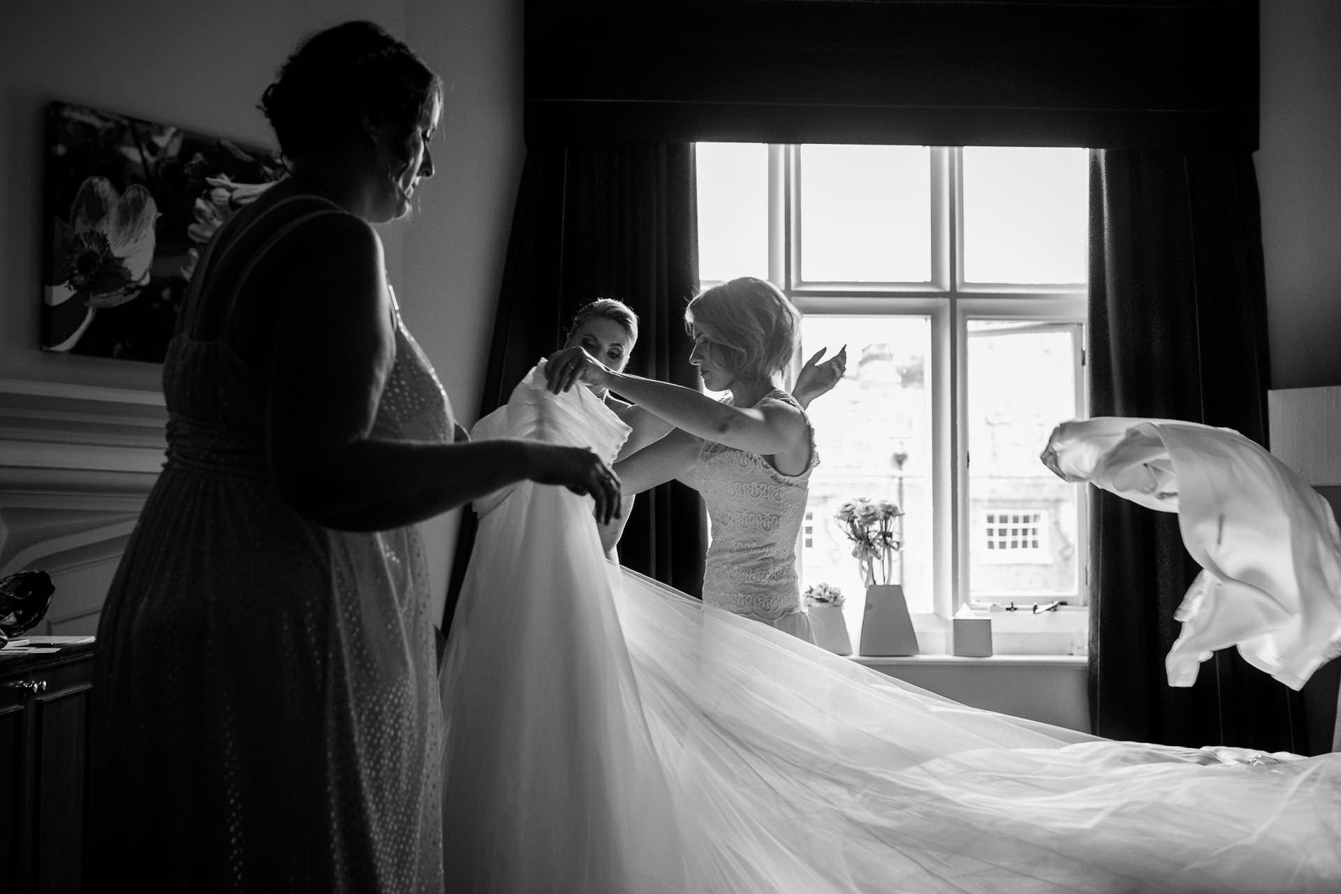 Wotton House wedding bride getting into the dress