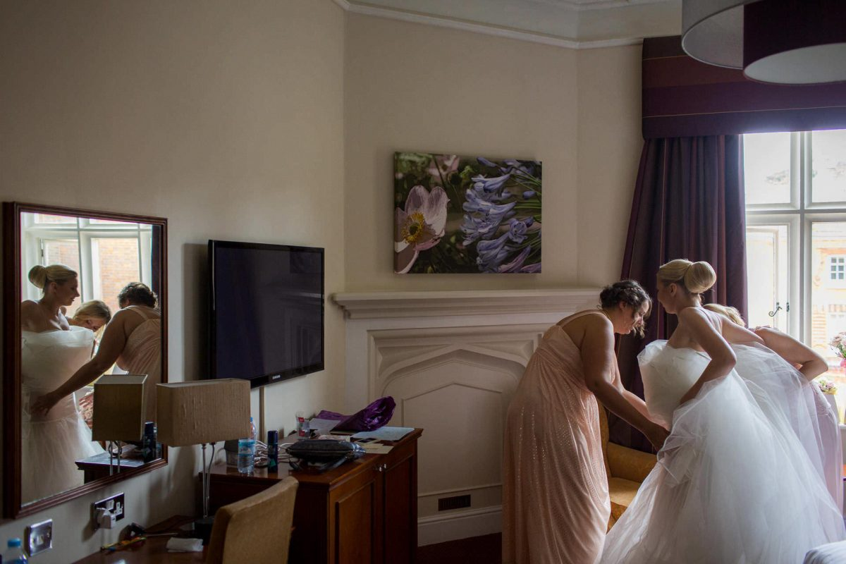 Wotton House wedding bridesmaids helps to put on dress