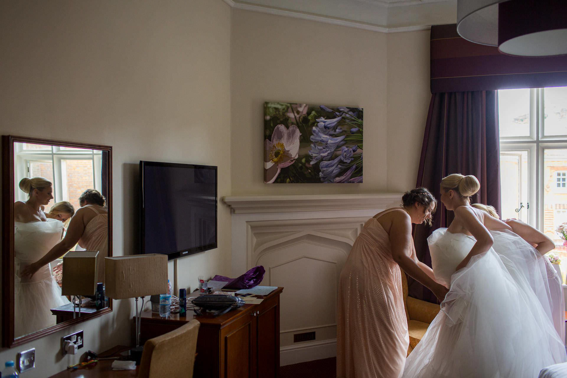 Wotton House wedding bridesmaids helps to put on dress