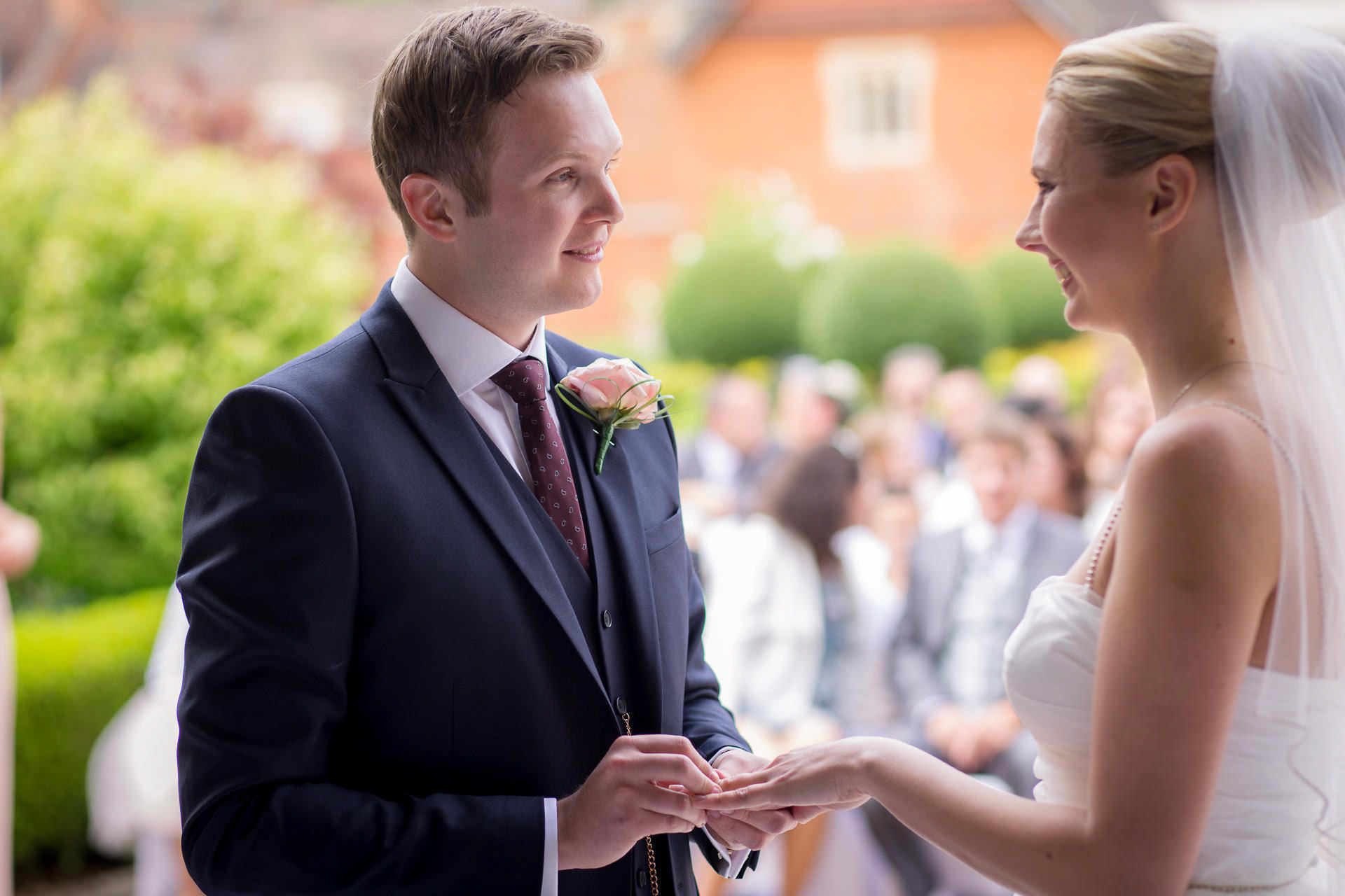 Wotton House wedding groom puts ring on the bride finger