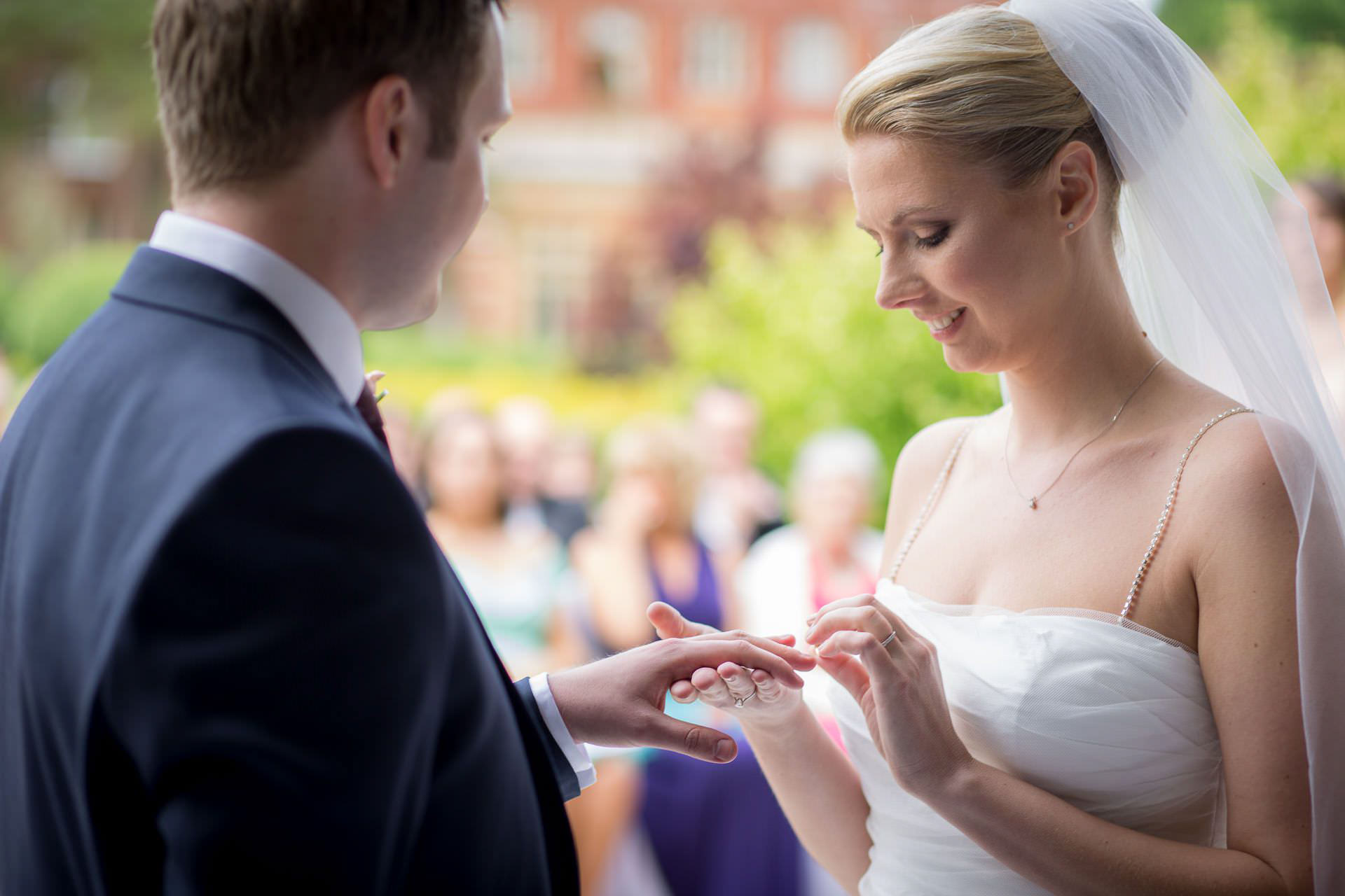 Wotton House wedding bride puts ring on grooms finger