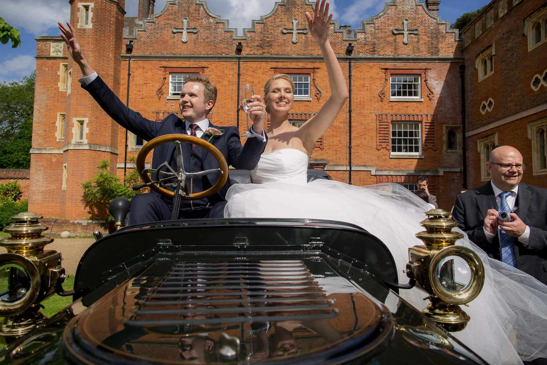 Wotton House wedding bride and groom raising hand seating in the car