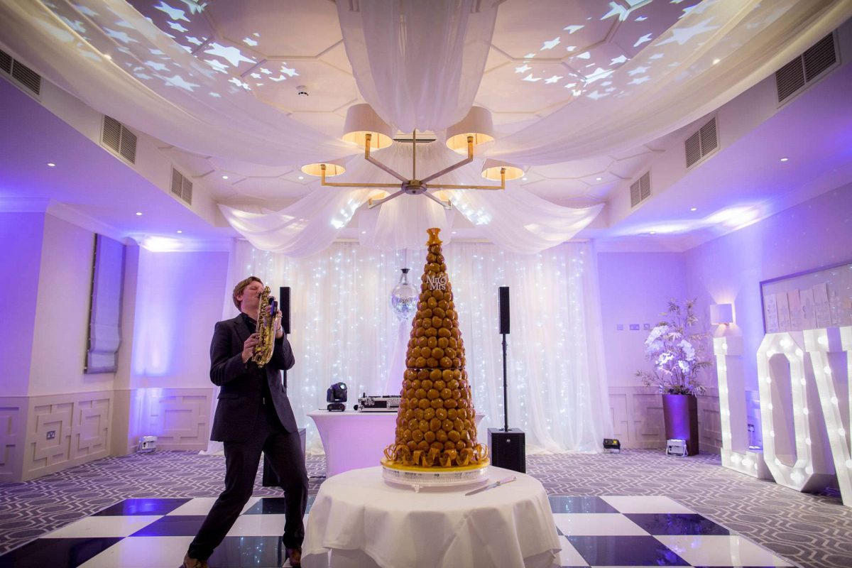 Wotton House wedding saxophonist next to the wedding cake