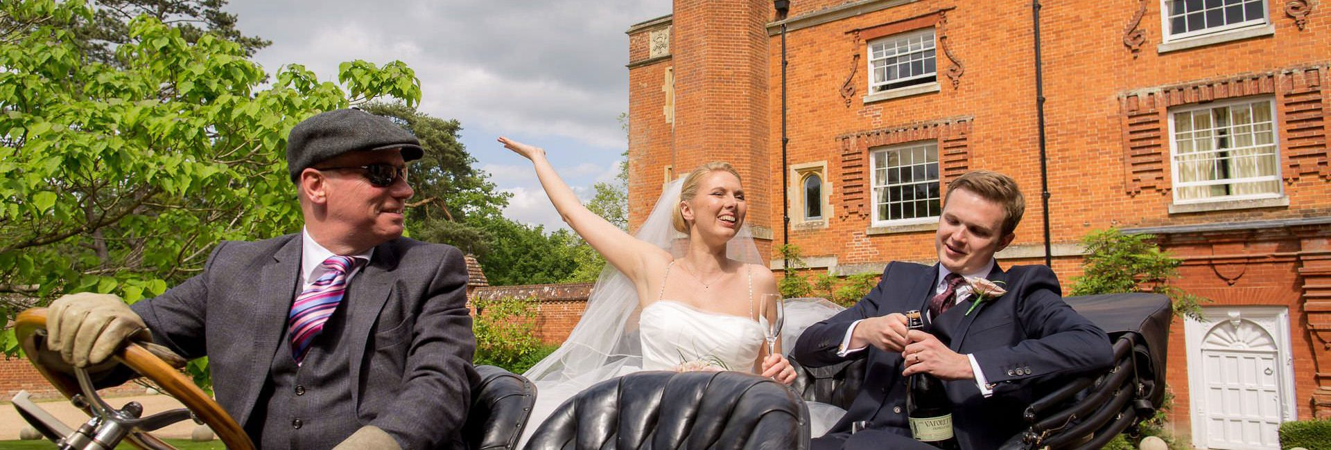 Wotton House wedding bride and groom open the champagne
