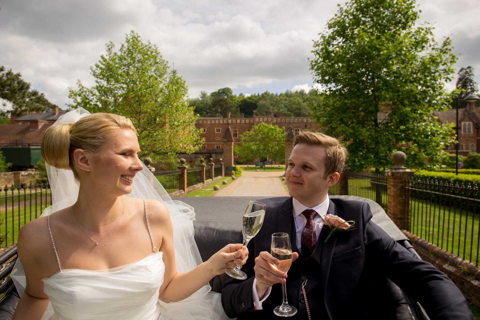 Wotton House wedding married couple drink Champagne in the car