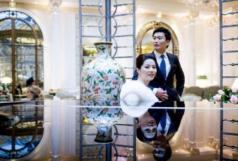 Chinese Wedding Bride and Groom by the piano in the hotel with the reflection of the black surface of the piano