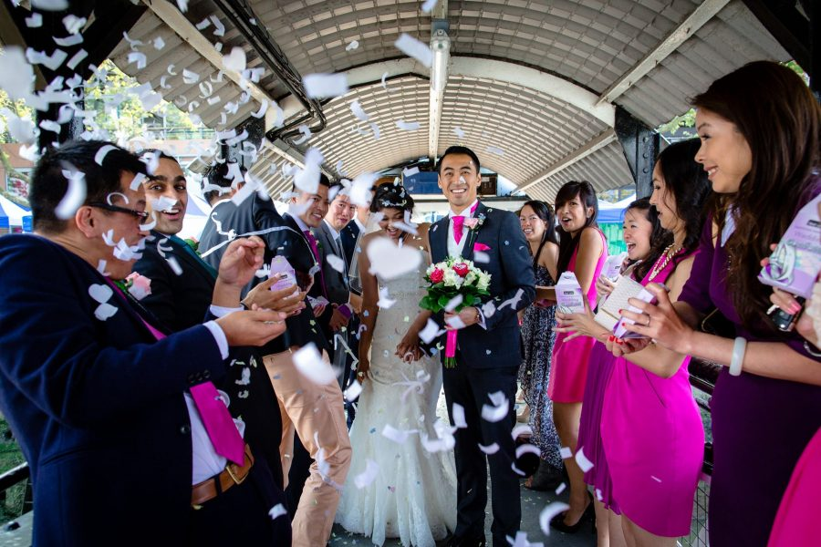 Chinese wedding couple under confetti on a bridge