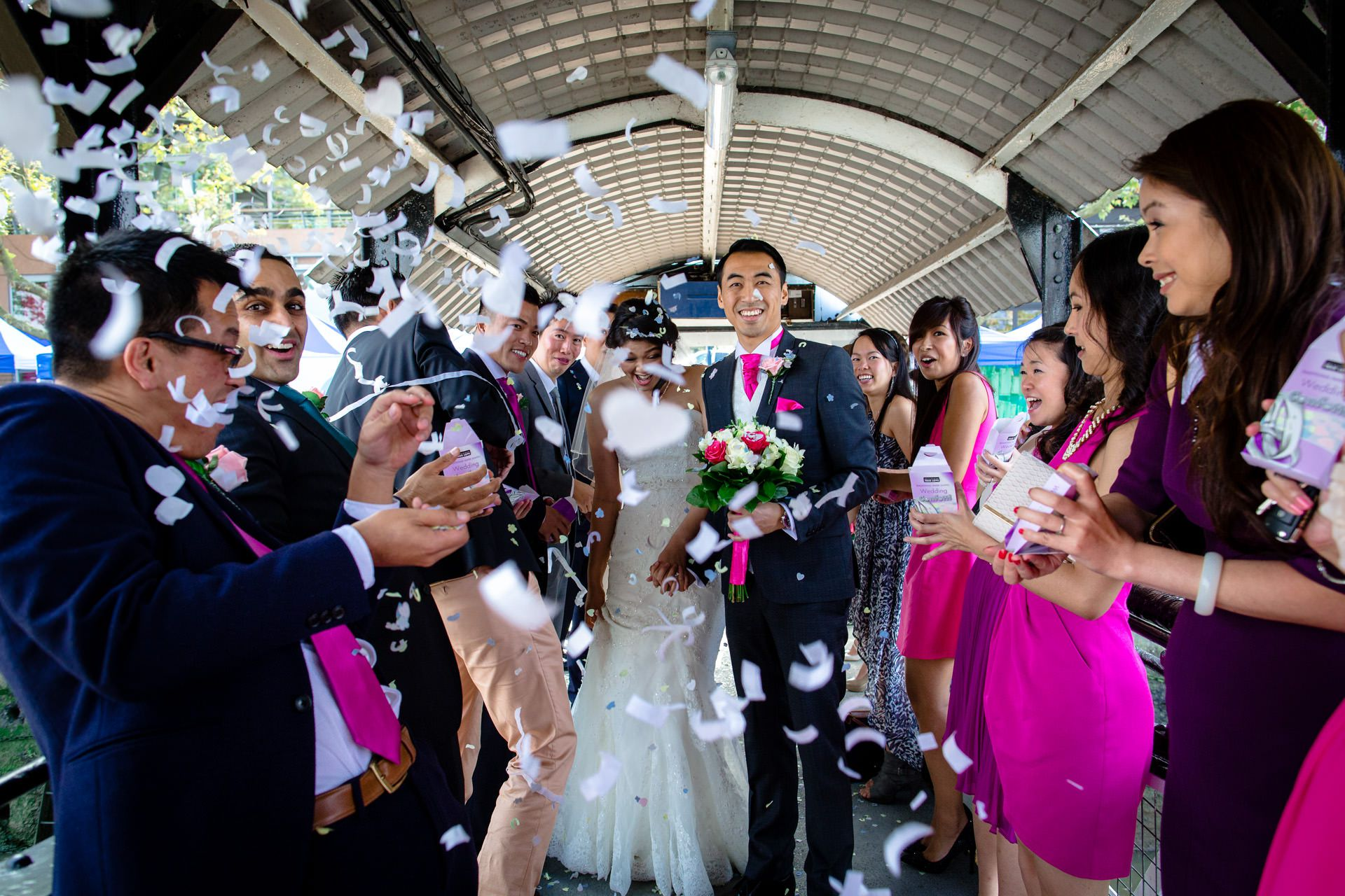 Chinese wedding couple under confetti on a bridge