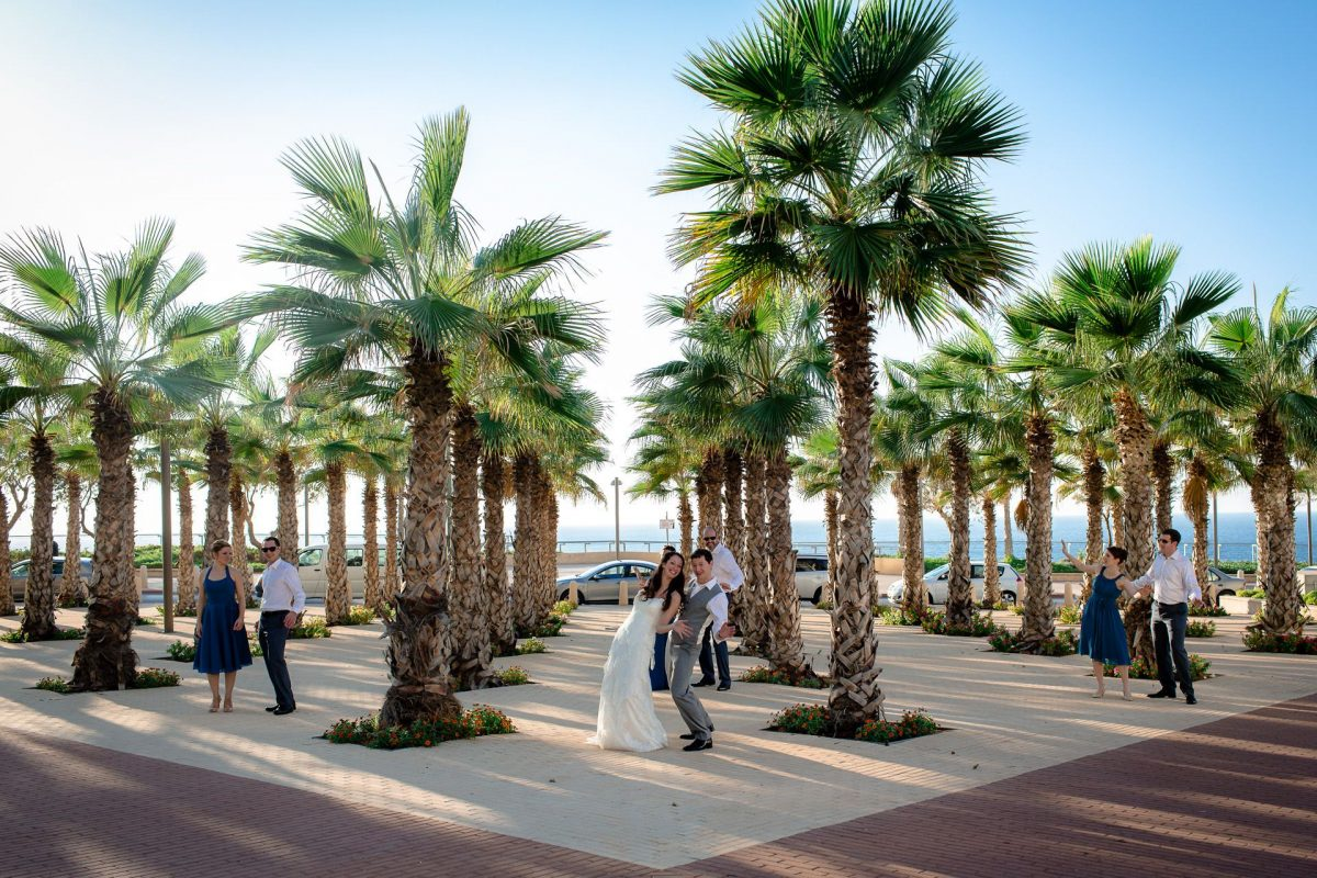 bride and groom are are posing among palms near the beach before they go to the venue to get married at their chosen destination