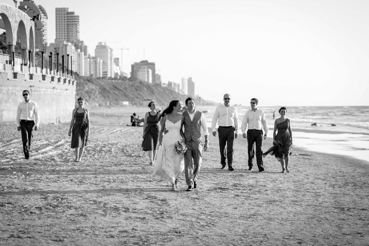 reservoir dogs walk on the beach with bride and groom and the wedding party on their destination wedding in Israel