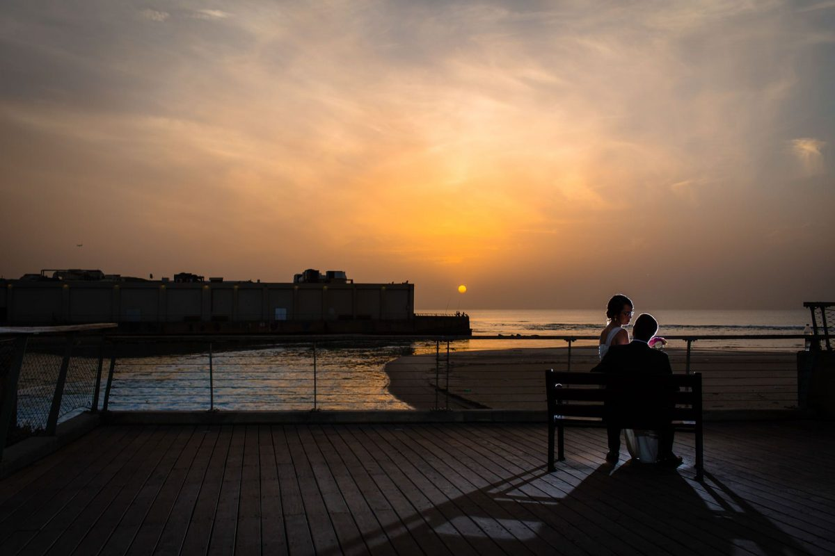 destination wedding photography at the sunset at the seaside with the couple cuddling on the bench
