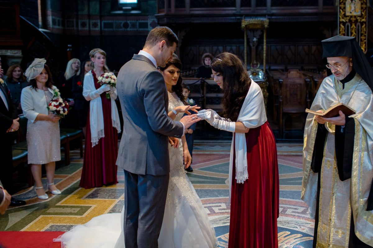 the sister of the bride is swapping the marriage rings on the fingers of the bride and groom