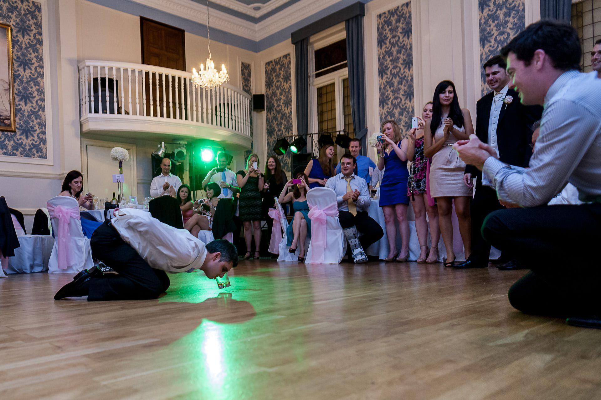 Greek Wedding Photo of groom drinking whiskey from the floor dance