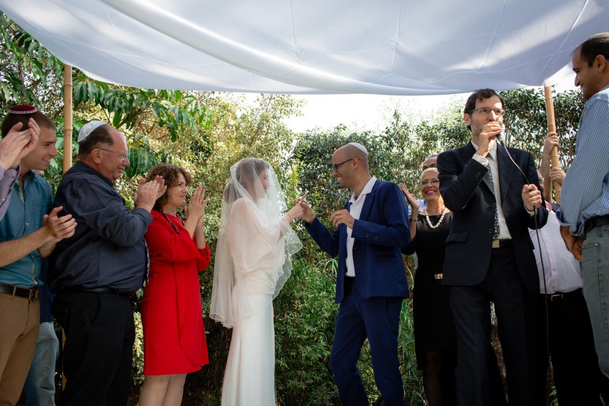 jewish groom putting a ring on the bride under chuppah