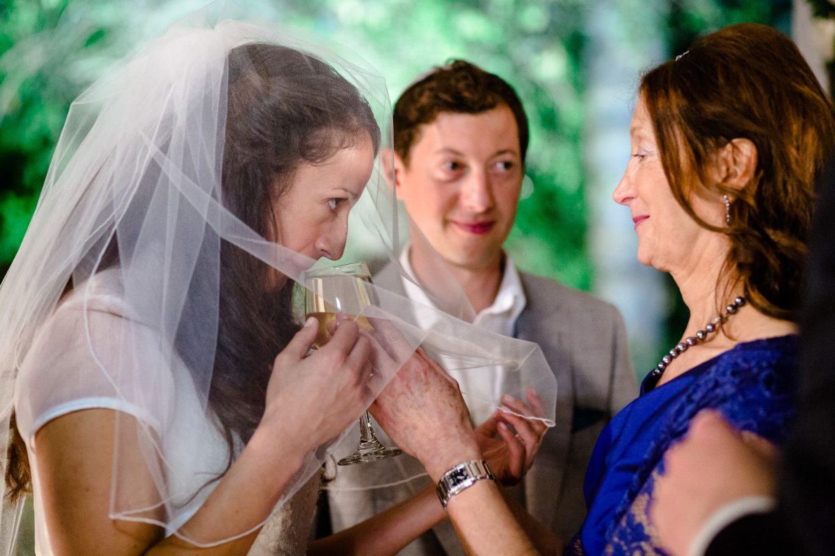 Jewish bride drinking wine under chuppah