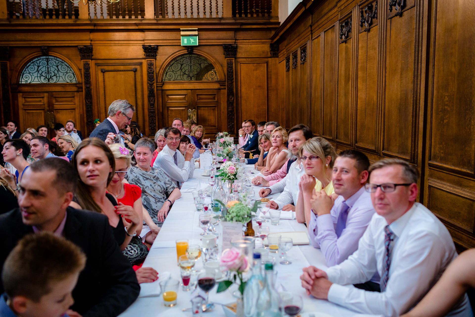 many guests at the long wedding table are listening the speach