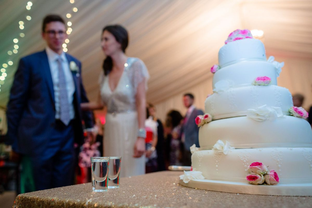 wedding cake on the first plan and couple on the background