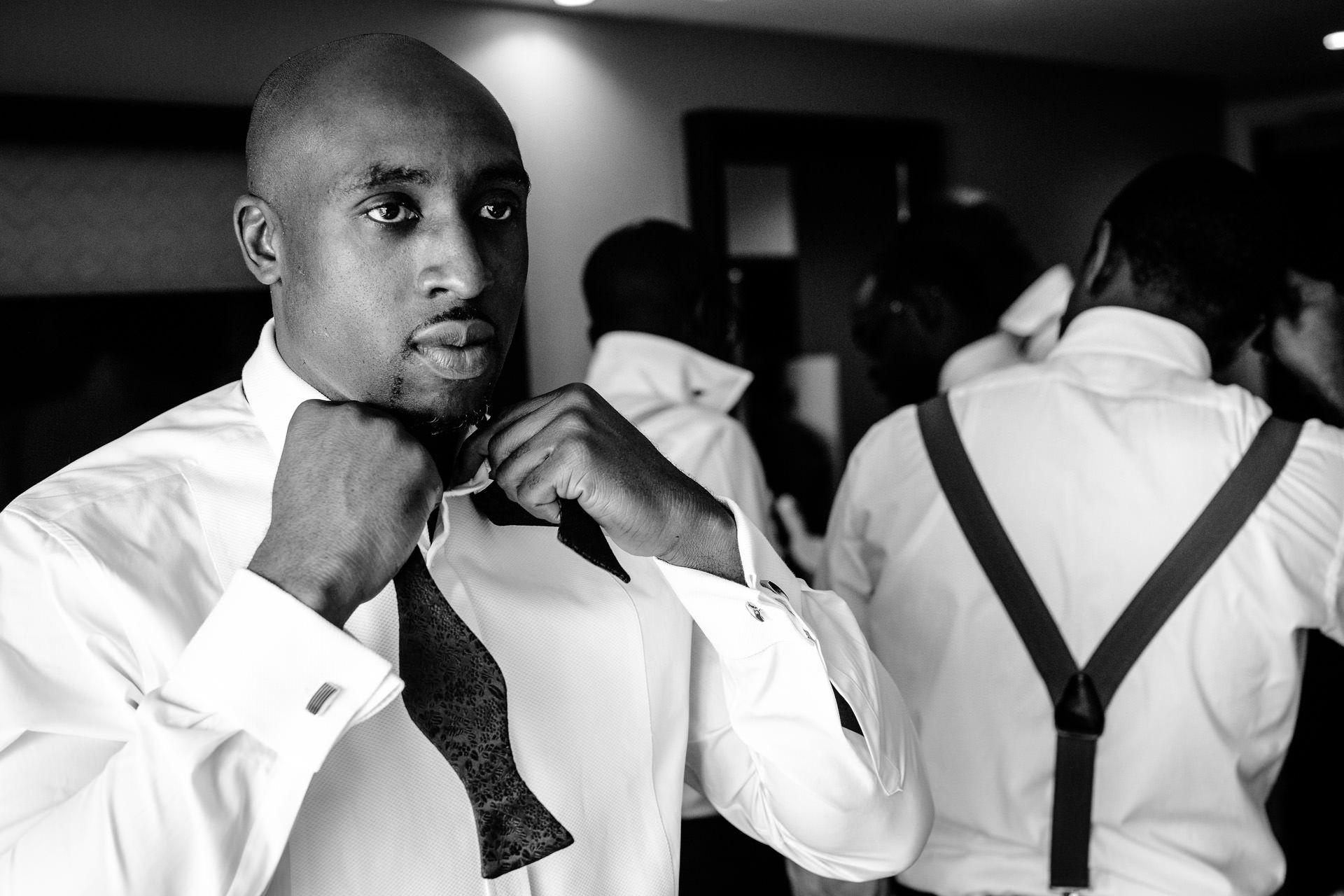 Nigerian wedding groom fixing his tie