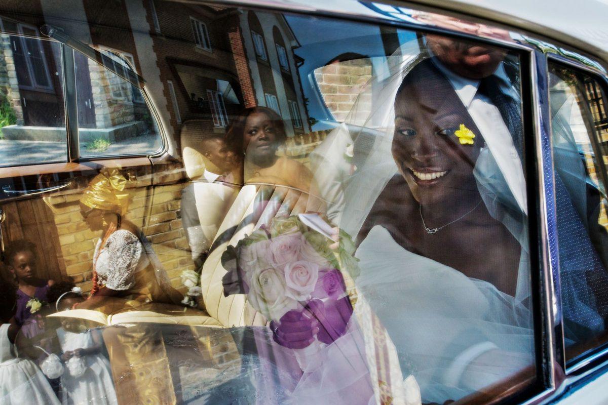 Nigerian bride in the car behind the glass window