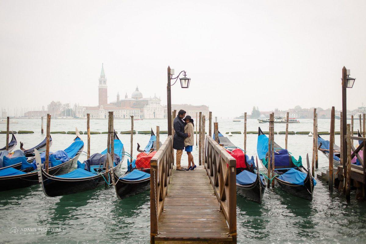 the couple between gondolas on a wooden bridge in Venice