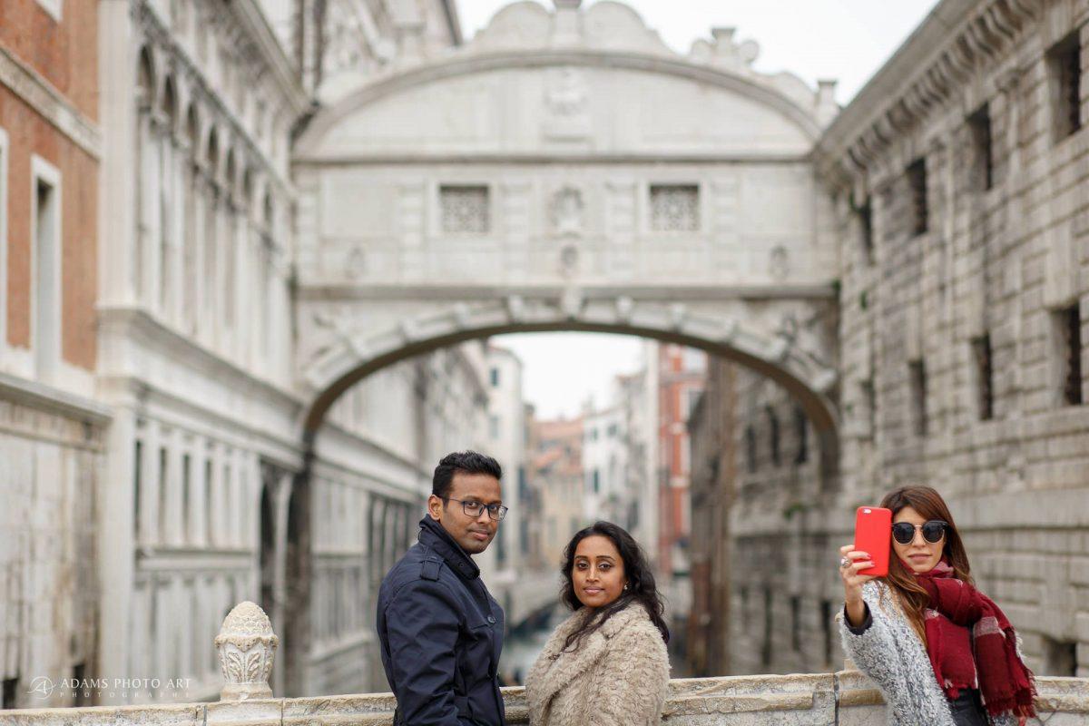 the engaged couple in front of the bridge ponte de suspiro in Venice
